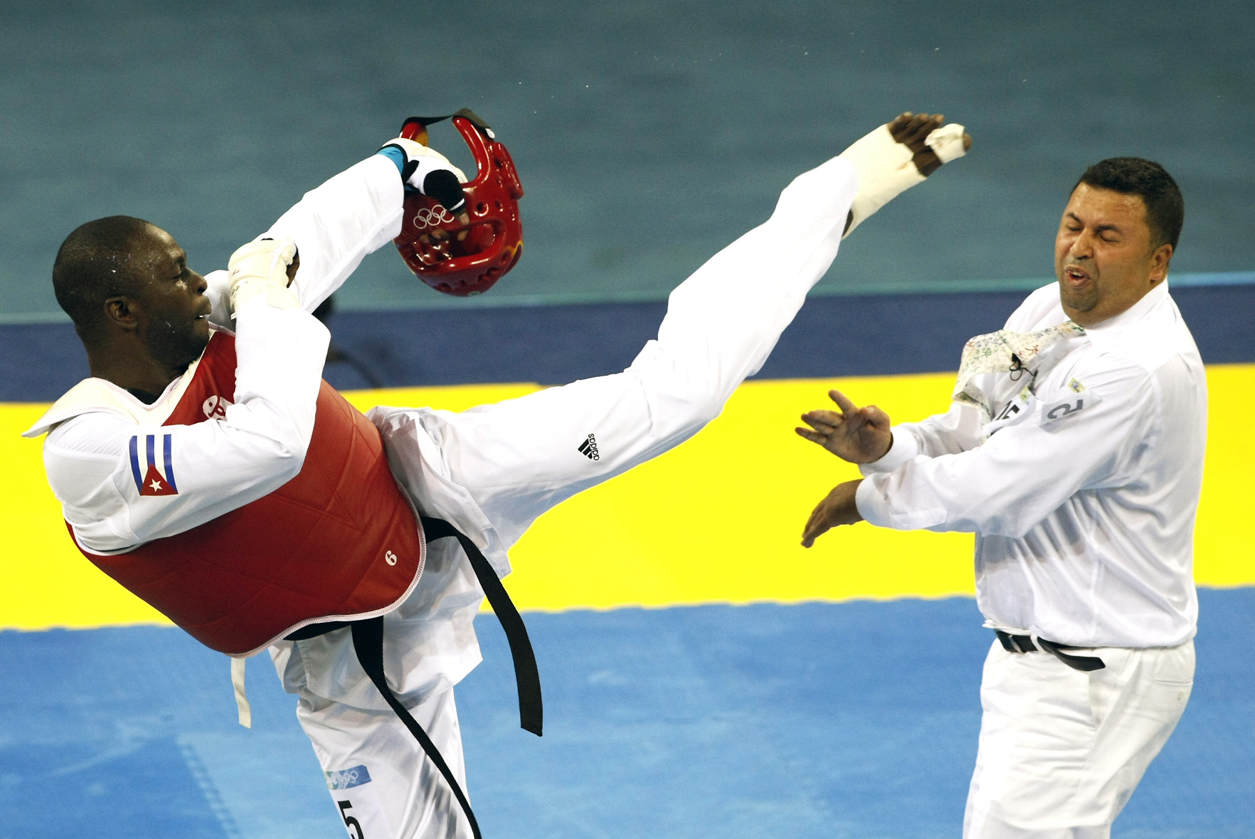 Angel Valodia Matos Of Cuba Kicks Out At The Referee During The Men's +80kg Bronze Medal Taekwondo Competition Against Arman Chilmanov Of Kazakhstan At The Beijing 2008 Olympic Games